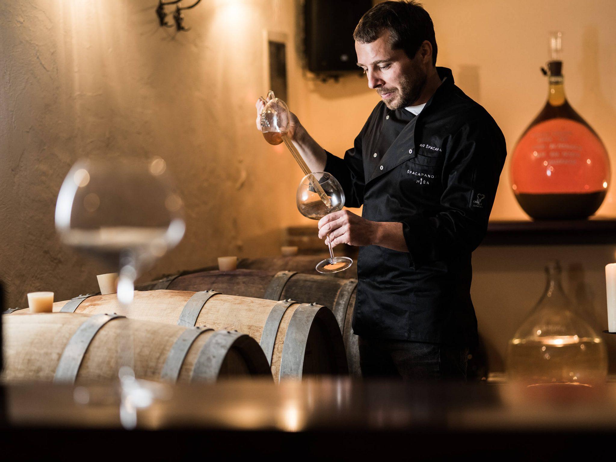 Ago Špacapan v kleti Špacapanove hiše okuša domače vino